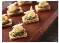 Crostini de queijo de castanha com pesto de manjericão e cebolas caramelizadas